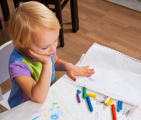 baby girl painted with colored crayons