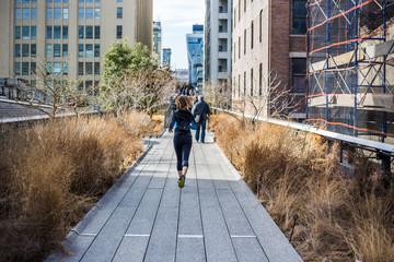 Inspiring shot of woman jogging on New York City High Line walkway
