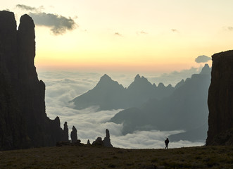 A hiker silhouetted and spire rock faces in an epic landscape with sharp mountain tops breaking through the clouds at sun rise.
