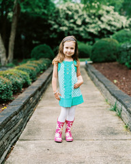 Cute young and fashionable girl standing on a sidewalk