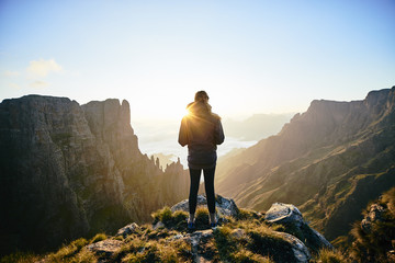 Female hiker admiring an epic spired mountain valley at sunrise.