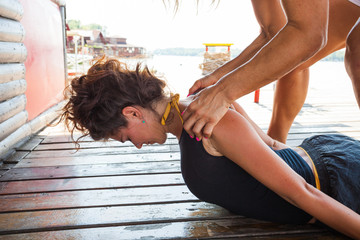 fitness instructor assisting young woman in stretching  exercise