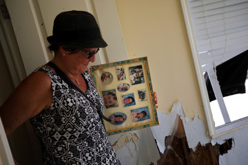 Lora Castelo rescues a frame with pictures of her children as she walks inside of her destroyed trailer home after Hurricane Irma struck Florida, in Islamorada