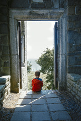 boy sits on the doorstep of an old house and looks at the sea. kid sitting alone on the steps near the house