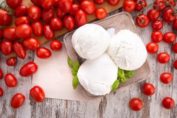 Tre mozzarelle intere di latte di bufala in un piatto di legno su un tavolo con pomodorini rossi