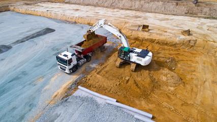 Photo aérienne d'une pelleteuse chargeant un camion sur un chantier