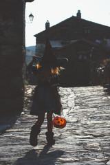 Kid with pumpkin in Halloween