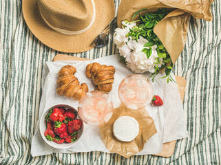 French style summer outdoor picnic setting. Flat-lay of glasses of rose wine, strawberries, croissants, brie cheese on board, straw hat, sunglasses, peony flowers, top view. Outdoor gathering concept