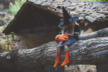 Cheerful kid in costume posing on tree