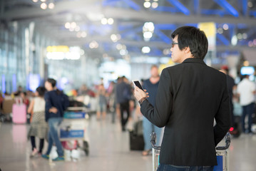 Young asian man using smartphone in airport terminal