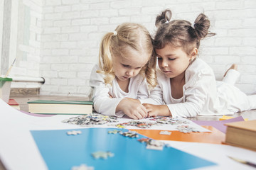 Two children, little girls of preschool age put the puzzle together on the floor