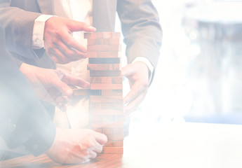 Blurred image,businessman hand and wood block stack game tower, activity success team work concept, vintage color tone process