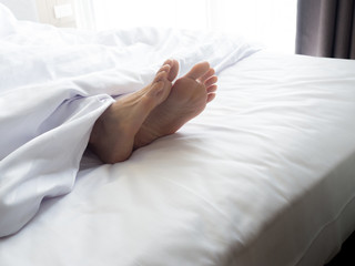 Feet of sleeping woman in white bed room.feet of a young woman lying in bed close up.