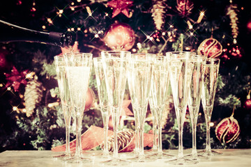 Wall Mural - Filling up glasses for party. Glasses of champagne with Christmas tree background and sparkles. Holiday season background. Traditional red and green Christmas decoration