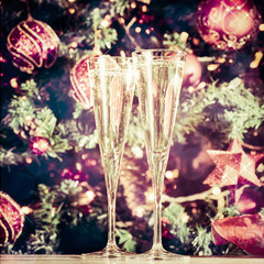 Fototapete - Two glasses of champagne with Christmas tree background and sparkles. Holiday season background. Traditional red and green Christmas decoration