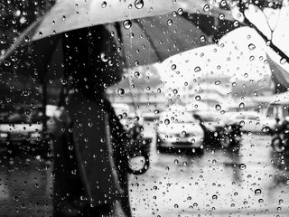 KUALA LUMPUR - SEPTEMBER 8, 2017: View of raindrops on the glass window during raining day with blurred woman walking in the rain.