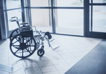 Solitary wheelchair resting in the lobby of a hospital. Abstract healthcare and disability image