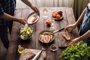 Couple cooking together shrimp dinner and salad of vegetables