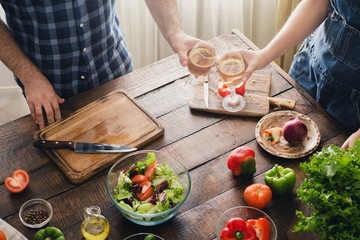 Couple cooking together delicious and healthy dinner and drinks wine