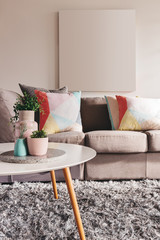 Modern living room sofa with blank artwork on the wall