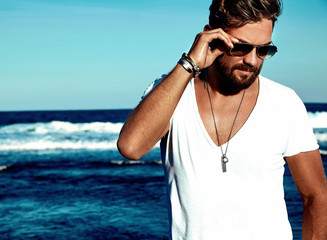 Portrait of handsome fashion man model wearing white clothes posing on blue sea background. In aviator sunglasses