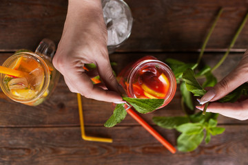 Waiter decorates fruit cocktails by mint. Fresh citrus and strawberry cold drink with ice on wooden table, concept of refreshment and satisfying thirst in summer, top view picture