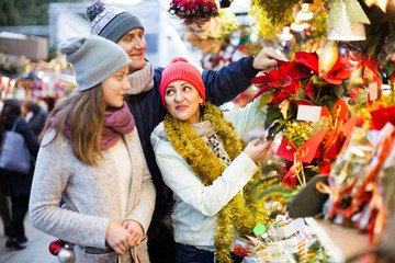 family of three with teenage girl choosing  floral decorations  at market. Shallow depth of focus