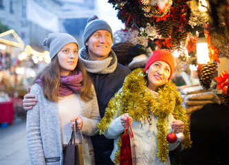 Happy married couple with a teenage daughter at Christmas market