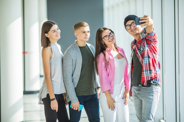 Happy four friends taking self portrait through smart phone in college