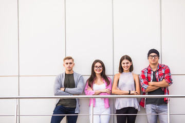 Group of four young smiling people wearing stylish casual clothing looking at camera standing in light office or university.