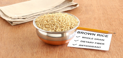 Brown rice, which is a whole grain and healthy food, in a copper bowl, with a note of some of its benefits, on a wooden background.