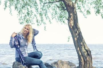 Blonde funny happy pretty romantic woman in the park near river. Sunny day.