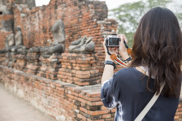 People back view,photographer woman take photo Old Buddha at Wat Phra Sri Sanphet temple,Ayutthaya,Thailand.Asian traveler female sightseeing with mirrorless camera.Travel and Photographer concept.