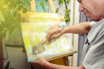 an old man on retirement is drawing a picture as hobby