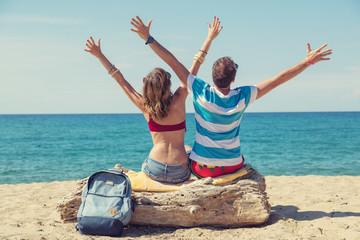 Happy couple enjoying vacation on a sandy beach.