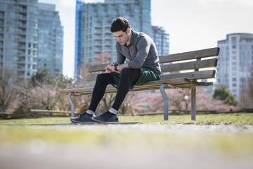 Surface level of young man checking time while sitting on bench