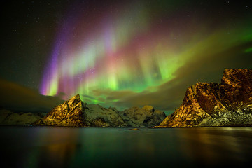 Aurora borealis (Polar lights) over the Lilandstinden mountain peak - Reinefjorden, Lofoten islands, Norway