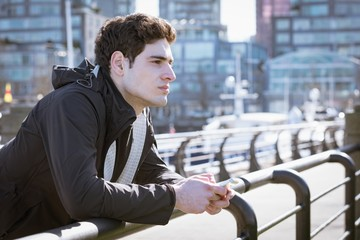 Thoughtful young man holding phone while leaning on railing