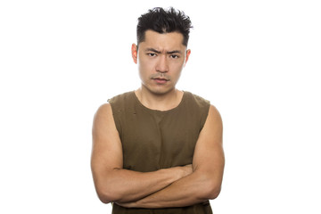 Athletic Asian male with trendy torn sleeveless shirt on a white background.  He is displaying angry expressions or gestures.  The handsome chinese or japanese man is muscular and physically fit