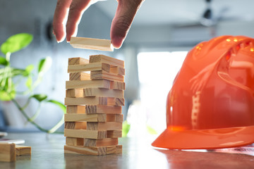 Hand of engineer  playing a blocks wood tower game of architectural project with sun flare and blur background .Selected focusing .