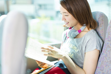 Young Woman reading Book in Bus