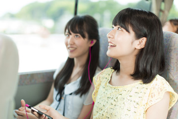 Two Young Women Sharing Headphone on Bus