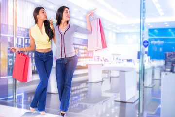 woman friends holding shopping bags and money excited to shopping in the shopping mall