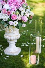 vases with tender pink flowers outdoor on the grass. Wedding decorations and floristic