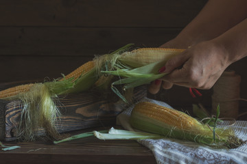 Fresh sweet corn on cobs on rustic wooden table, close up. Toned. Shallow depth of field.