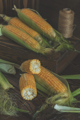 Foto op Plexiglas Spa Fresh sweet corn on cobs on rustic wooden table, close up. Toned. Shallow depth of field.