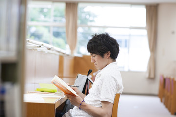 Male College Student Studying in Library