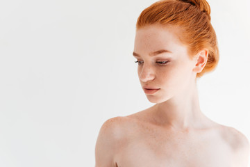Close up picture of attractive naked ginger woman looking away