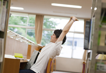 Male College Student Stretching in Library
