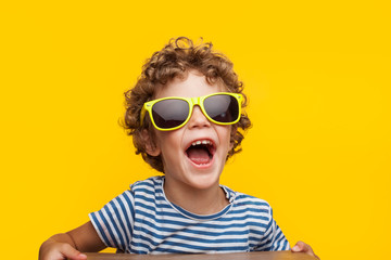 Adorable kid in bright sunglasses on orange Wall mural